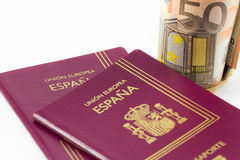Spanish passport with european union currency banknotes Royalty Free Stock Photos