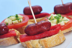 Spanish pinchos. Closeup of a plate with spanish pinchos, typical northern sandwiches, some of them made with chorizos an piquillo peppers stock images