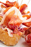 Spanish pinchos de jamon, serrano ham served on bread. Closeup of a plate with some typical spanish pinchos de jamon, serrano ham served on bread royalty free stock photo