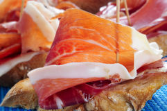 Spanish pinchos de jamon, serrano ham served on bread. Closeup of a plate with some typical spanish pinchos de jamon, serrano ham served on bread as tapas royalty free stock photography
