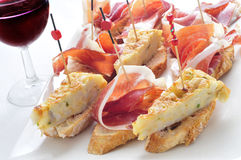 Spanish pinchos, spanish tortilla and serrano ham served on brea Royalty Free Stock Photos