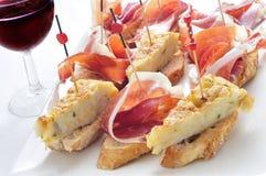 Spanish pinchos, spanish tortilla and serrano ham served on brea Royalty Free Stock Photos