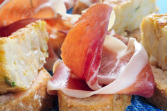 Spanish pinchos: spanish tortilla and serrano ham served on brea Stock Photos
