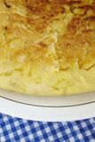 Spanish potato omelette detail on a dish and blue tablecloth Stock Photography