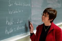 Spanish Professor. Middle-aged female Spanish professor at blackboard royalty free stock image
