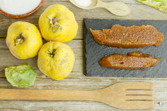 Spanish quince fruits and paste with ingredients. On wooden background Stock Images