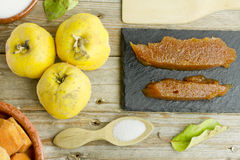 Spanish quince fruits and paste with ingredients. On wooden background Royalty Free Stock Photography