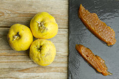 Spanish quince paste. On a slate plate with three quince fruits on wooden background Royalty Free Stock Images