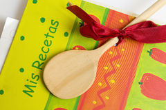 Spanish recipe book. Closeup of colorful Spanish recipe or cookery book with wooden spoon and ribbon Stock Images