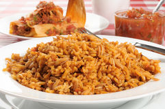 Spanish rice. A bowl of Spanish or Mexican rice with tamales in the background Royalty Free Stock Images