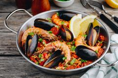 Spanish seafood paella with mussels, shrimps and chorizo sausages in traditional pan. On wooden background stock image
