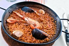 Spanish seafood paella in rustic pan Stock Photos
