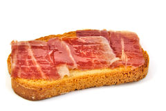 Spanish serrano ham on bread slice. White Royalty Free Stock Images