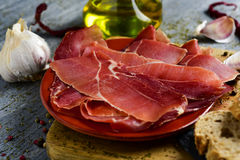 Spanish serrano ham. Closeup of an earthenware with some slices of spanish serrano ham on a wooden chopping board, and some slices of bread and a glass cruet Stock Photos