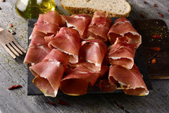 Spanish serrano ham. High-angle shot of some slices of spanish serrano ham on a wooden chopping board, and some slices of bread and a glass cruet with olive oil Stock Image