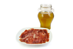 Spanish serrano ham with olive oil on white Stock Photography