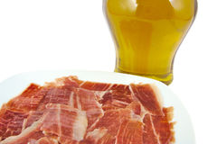 Spanish serrano ham with olive oil on white Stock Images