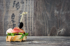 Spanish serrano ham skewer with olives and lettuce on a rustic wooden background Stock Photo