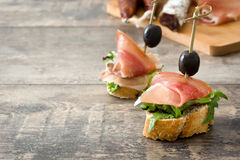Spanish serrano ham skewers with olives and lettuce on a rustic wooden background Stock Photo