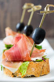 Spanish serrano ham skewers with olives and lettuce on a rustic wooden background Royalty Free Stock Images