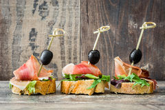 Spanish serrano ham skewers with olives and lettuce on a rustic wooden background Royalty Free Stock Photo