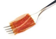 Spanish serrano ham slice on metal fork. Stock Photo