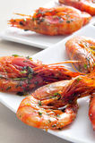 Spanish shrimps with garlic and parsley. Closeup of a plate with spanish shrimps cooked with garlic and parsley, on a set table Stock Images