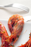 Spanish shrimps with garlic and parsley. Closeup of a plate with spanish shrimps cooked with garlic and parsley on a set table Royalty Free Stock Photos