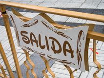 Spanish signboard of exit. In the fence stock photo