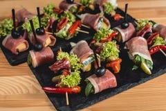 Spanish snack, banderillas on skewers with jamon, ramses, pear, dorblue, chorizo, dried tomato, champignon, pickling Royalty Free Stock Photos
