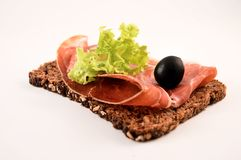 Spanish snack (tapas). Dark slice of bread with jamon serrano, lettuce and a black olive Royalty Free Stock Photos