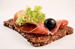 Spanish snack (tapas). Slice of dark bread with ham, lettuce and a black olive Royalty Free Stock Images