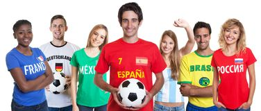 Spanish soccer fan with ball and cheering group of other fans stock image