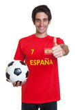 Spanish soccer fan with black hair and ball showing thumb up Royalty Free Stock Images