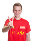 Spanish sports fan with blond hair showing victory sign Royalty Free Stock Photography