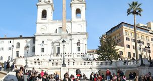 Spanish Steps Rome. ROME, ITALY - JANUARY 27, 2018: People sitting on the Spanish Steps enjoying the sunny day. Spanish Steps and Trinita dei Monti church are stock video footage