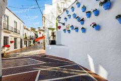 Spanish street with blue flower pots on a white wall. stock photo