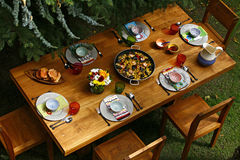 Spanish style dining table with paella, overview. Spanish style dining table with paella and Spanish style dishes on wooden table in backyard. Overview Royalty Free Stock Photos