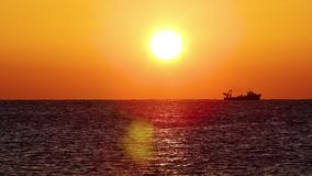 Spanish sunrise over the ocean with fisher boat stock video footage