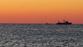 Spanish sunrise over the ocean with fisher boat stock footage
