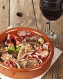 Spanish tapa, setas con jamon. Oyster mushrooms, serrano ham and pine nuts tapas.  Setas con jamon y pinones with rioja red wine Stock Image
