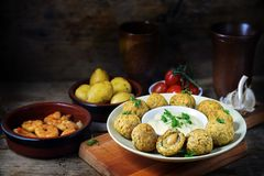 Spanish tapas appetizers such as baked olives, prawn shrimps, po. Tatoes, tomato and garlic sauce on a dark rustic wooden background, copy space, selective focus Royalty Free Stock Photos