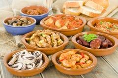 Spanish Tapas & Crusty Bread. Chorizo al vino, gambas pil pil, patatas bravas, albondigas a la jardinera, setas al ajillo, pollo al limon con ajo, rollitos de Stock Photo