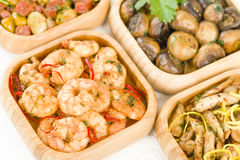 Spanish Tapas. Gambas Pil Pil (sizzling prawns), Pollo al limon con ajo (chicken with garlic), Setas al Ajillo (sauteed mushrooms with garlic) and Habas Con Stock Images