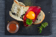 Spanish tapas with slices cured meat and yolk, close view from tiop. Dark photo. Spanish tapas with slices cured meat and yolk, close view from tiop. Dark photo royalty free stock images