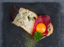 Spanish tapas with slices cured meat and yolk, close view from tiop. Dark photo. Spanish tapas with slices cured meat and yolk, close view from tiop. Dark photo stock image