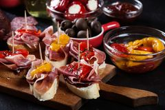 Spanish tapas with slices jamon serrano and grilled pepper. Also olives, salami, pickled onions, and peppers stuffed with cheese. Spanish cuisine stock photography