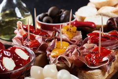 Spanish tapas with slices jamon serrano and grilled pepper. Also olives, salami, pickled onions, and peppers stuffed with cheese. Spanish cuisine royalty free stock photography