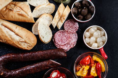 Spanish tapas with slices jamon serrano and grilled pepper. Also. Olives, salami, pickled onions, and peppers stuffed with cheese. Spanish cuisine. Top view royalty free stock photo