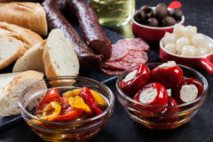 Spanish tapas with slices jamon serrano and grilled pepper. Also olives, salami, pickled onions, and peppers stuffed with cheese. Spanish cuisine royalty free stock photos